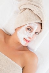 Attractive having white cream on her face at spa center