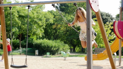 Young woman in skirt on swing in summer