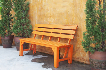orange wooden bench against concrete wall