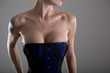 Busty young woman in black and blue corset