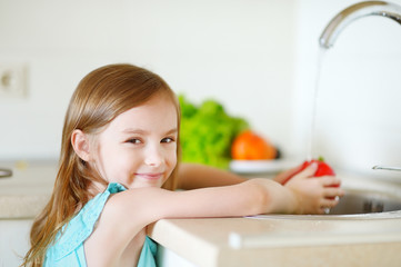 Adorable girl washing vegetables in a kitchen