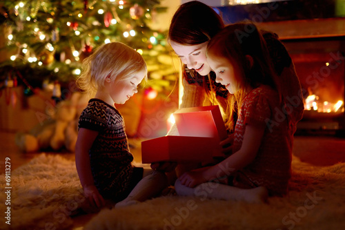 Mother and her daughters opening a Christmas gift - 69113279