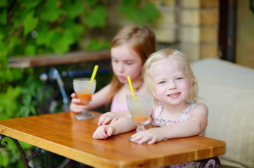 Two sisters drinking juice in outdoor cafe