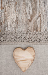 Wooden heart on the lace fabric and old wood