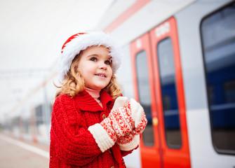 Little girl in Santa costume on the train platform