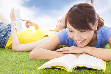 smiling pretty students lying on the grassland with books