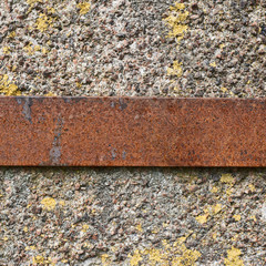 Rusty metal strip over the concrete wall