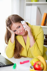 Beautiful young tired woman talking on the phone in the office