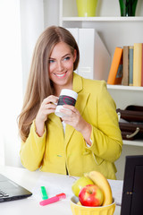 Beautiful young secretary drinking a cup of tea in the office