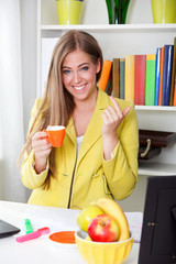 Beautiful young secretary drinking coffee in the office
