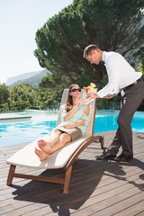 Waiter serving woman breakfast by swimming pool