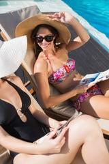 Women reading books on sun loungers by swimming pool