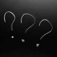 Three question marks on the blackboard