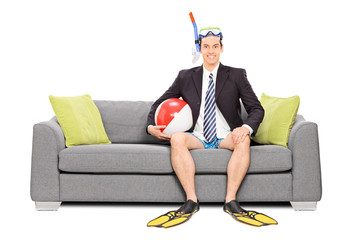 Man with snorkel and business suit seated on sofa