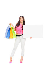 Woman holding shopping bags and a blank banner