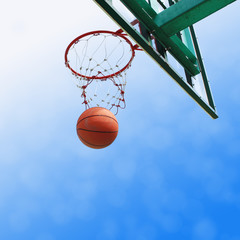 basketball drop into the orange metal goal and white net.