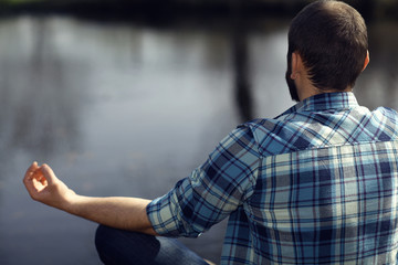 man meditating on the bank of a pond