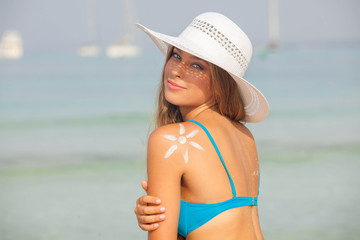 concept for safe sunbathing, woman with sun cream