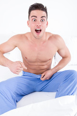 handsome half naked man having problems with genitals and potenc