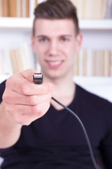 man holding black USB cable