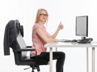 Geschäftsfrau am Schreibtisch zeigt Daumenhoch