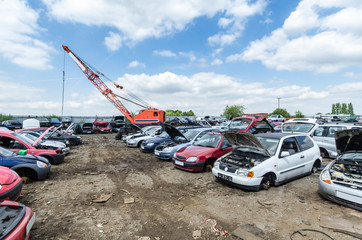 Crane at a car scrapyard moving metal