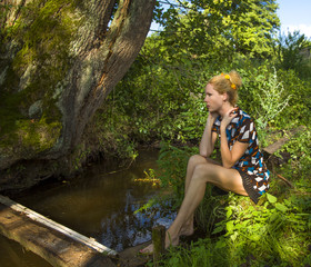 The girl sat down to have a rest near the small river