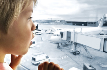 Cute boy looking at planes in the airport with great interest