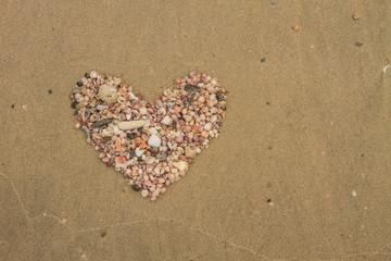 Heart made of sea shells lying on a beach sand