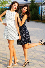 Two young girls friends wearing nice dresses