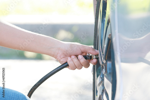 woman inflating car tire. - 69125063
