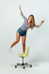 girl standing on a chair balancing