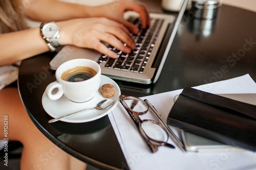 Leinwandbild Motiv Young business woman in cafe drinking coffee with laptop