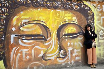 Traveler Thai Women with wall painting on street in Kathmandu