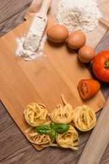 Raw pasta, tomato and eggs