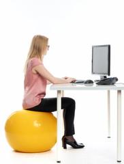 Geschäftsfrau mit Sitzball am Schreibtisch