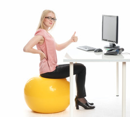 Geschäftsfrau sitzt auf einem Sitzball am Schreibtisch