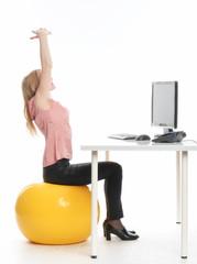 Geschäftsfrau am Schreibtisch macht Entspannungsübungen