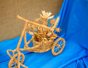 The original souvenir made of wattled straw against blue silk.