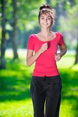 Runner - woman running outdoors in green park