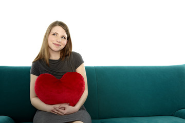 Beautyful young woman with heart shaped pillow