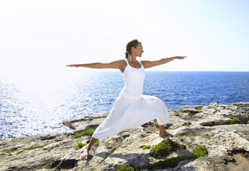 Yoga posture on rocks near the ocean