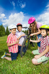 Happy kids in colorful helmets repair bike