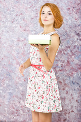 Charming young girl holding a gift box