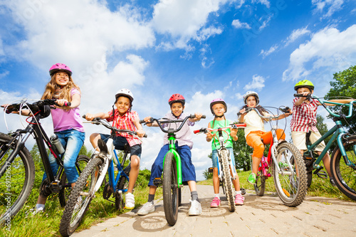 Below angle view of kids in helmets with bikes - 69129637