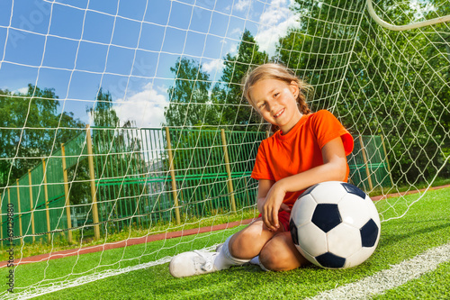canvas print picture Smiling girl with bending arm on football sitting
