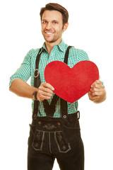 Mann in Lederhose hält rotes Herz