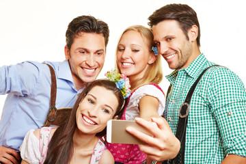 Freunde in bayrischer Tracht fotografieren sich mit Smartphone