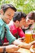 Leute schauen auf Smartphone im Biergarten
