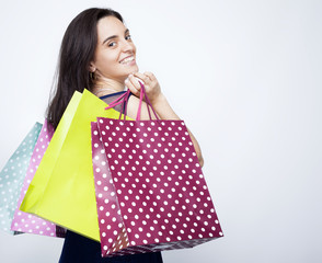 Happy young woman with colored shopping bags over gray backgroun